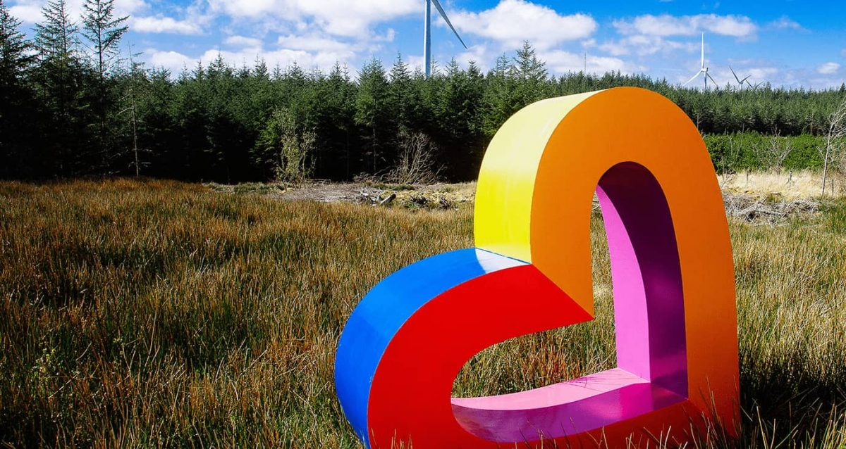 A colourful heart in a field in front of a forest